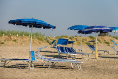Tomma solstolar under paraplyer på stranden fotografering för bildbyråer
