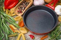Tomma stekpanna, grönsaker och kryddor på träbakgrund royaltyfria bilder