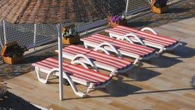 Tomma sunbeds nära hotellet och stranden Morgon på en strand, stranden med soldagdrivare och solparaplyer stock video