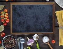 Tomma svarta ram och ingredienser för att laga mat pasta royaltyfri foto