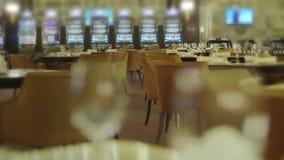 Tomma tabeller med vinexponeringsglas i restaurang nära enarmade banditer i kasino stock video
