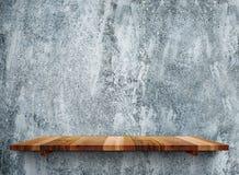 Tomma träshelfs på den gråa stenväggen för grunge, förlöjligar upp mall royaltyfri fotografi