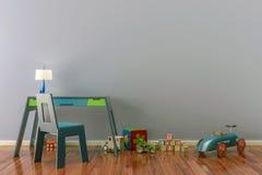 Tomma ungar hyr rum med leksaker, arbetar skrivbordet och stol Arkivfoto