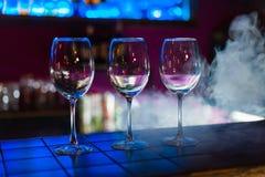 Tomma vinexponeringsglas i rad på stång eller restaurang arkivbild