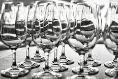 Tomma vinexponeringsglas i raden på tabellen Royaltyfri Bild