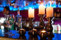 Tomma vinexponeringsglas och stearinljus med belysningljusbakgrund royaltyfri foto