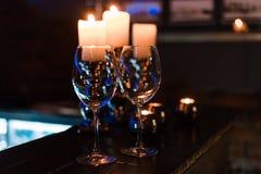 Tomma vinexponeringsglas och stearinljus med belysningljusbakgrund arkivbild