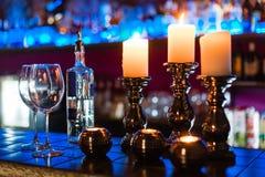Tomma vinexponeringsglas och stearinljus med belysningljusbakgrund arkivfoton