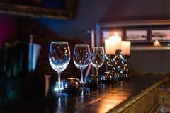 Tomma vinexponeringsglas och stearinljus med belysningljusbakgrund royaltyfria bilder
