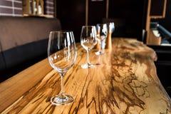 Tomma vinexponeringsglas på tjock skivatabellen i restaurang Royaltyfria Foton