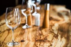 Tomma vinexponeringsglas på tjock skivatabellen i restaurang Fotografering för Bildbyråer