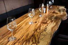 Tomma vinexponeringsglas på tjock skivatabellen i restaurang Arkivbild