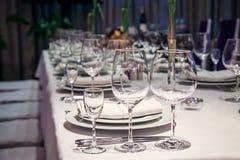 Tomma vinexponeringsglas som är ordnade på en tabell Royaltyfri Fotografi