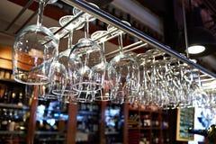 Tomma vinexponeringsglas som hänger ovanför stång Arkivfoton