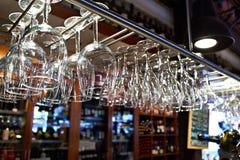 Tomma vinexponeringsglas som hänger ovanför stångräknare Royaltyfri Bild