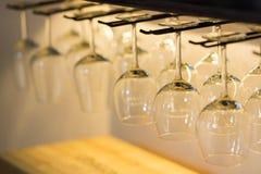 Tomma vinexponeringsglas som hänger på stångkuggen arkivbild