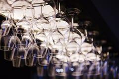 Tomma vinexponeringsglas som hänger upsidedown i stånginre Royaltyfria Foton