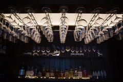 Tomma vinexponeringsglas som hänger upsidedown i stånginre Fotografering för Bildbyråer