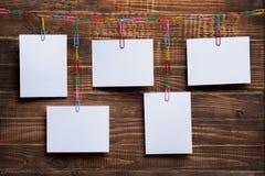 Tomma vita kort som hänger på gemkedja på en träbakgrund, en mall för en fotocollage, ett begrepp av minnen och ett foto royaltyfri foto
