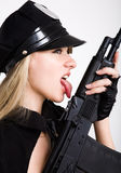 Tommy gun. Portrait of young woman licking with tongue black tommy gun royalty free stock image