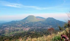 Tomohon stad och tvilling- volcanoes Arkivfoto