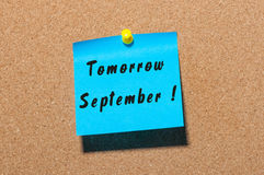 Tomorrow September. hand drawn lettering on color sticker pinned to notice corl board background stock photos
