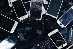 Mobile phone batteries, tablets, broken screens LCD iPhone. TOMSK, RUSSIA - June 29, 2017: Close-up of used mobile phone batteries, tablets, broken screens LCD royalty free stock image