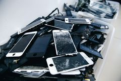 Mobile phone batteries, tablets, broken screens LCD iPhone. TOMSK, RUSSIA - June 29, 2017: Close-up of used mobile phone batteries, tablets, broken screens LCD royalty free stock images