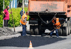TOMSK, RUSSIA - JUNE 4, 2016: Workers put asphalt on the road in Stock Images