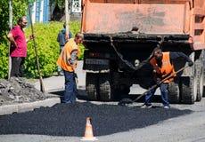 TOMSK RYSSLAND - JUNI 4, 2016: Satta arbetare asfalterar på vägen in Arkivbilder