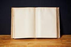 Tomt öppna boken på en ljus trähylla på den svarta väggen arkivfoto