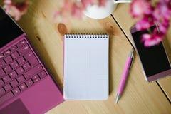 Tomt anteckningsbokpapper med bärbara datorn och smartphonen Arkivfoto