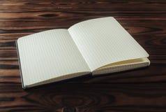 Tomt anteckningsbokpapper på träbakgrund Arkivfoto