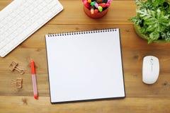 Tomt anteckningsbokpapper, tangentbord, mus och pennor på wood tabellbac Royaltyfri Fotografi