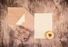 Tomt ark av papper, det öppna kuvertet och gåvaasken på träbräde letter romantiker Royaltyfri Bild