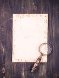 Tomt ark av papper och ett tappningförstoringsglas Royaltyfri Bild