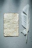 Tomt ark för tappning av pappersvingpennan på grå bakgrund Royaltyfria Foton