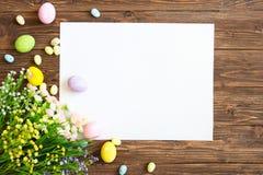 Tomt ark med easter garneringar på den bruna träbakgrunden tillgänglig hälsning för korteaster eps mapp Royaltyfri Fotografi