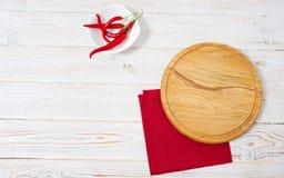 Tomt bitande skrivbord, chilipeper och röd servett på träbästa sikt för tabell royaltyfria foton