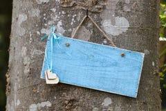 Tomt blått tecken med hjärtor som hänger på träd i skog Royaltyfri Fotografi