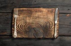 Tomt bräde för tappning med gaffeln och kniven arkivbilder