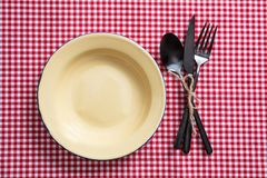 Tomt emaljplatta och bestick på den röda rutiga bordduken, bästa sikt arkivfoto