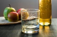 Tomt exponeringsglas, äpplen, äpplevin som är klart att dricka Royaltyfri Bild