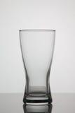 Tomt exponeringsglas av öl på vit bakgrund Arkivbild