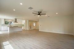 Tomt familjrum med kök i det Kalifornien hemmet med wood golv Arkivfoto