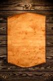 Tomt gammalt papper mot bakgrunden av ett åldrigt trä Arkivfoto