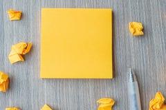 Tomt gult anmärkningspapper med pennan och smulat papper på trätabellbakgrund Tomt kopieringsutrymme f?r text ?gander?tt f?r home arkivbilder