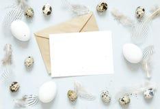 Tomt hälsa kort, kraft kuvert Påsksammansättning med easter ägg och fjädrar på blå bakgrund royaltyfri foto