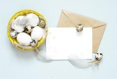 Tomt hälsa kort, kraft kuvert Påsksammansättning med easter ägg och fjädrar på blå bakgrund royaltyfri fotografi