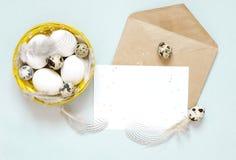 Tomt hälsa kort, kraft kuvert Påsksammansättning med easter ägg och fjädrar på blå bakgrund royaltyfri bild